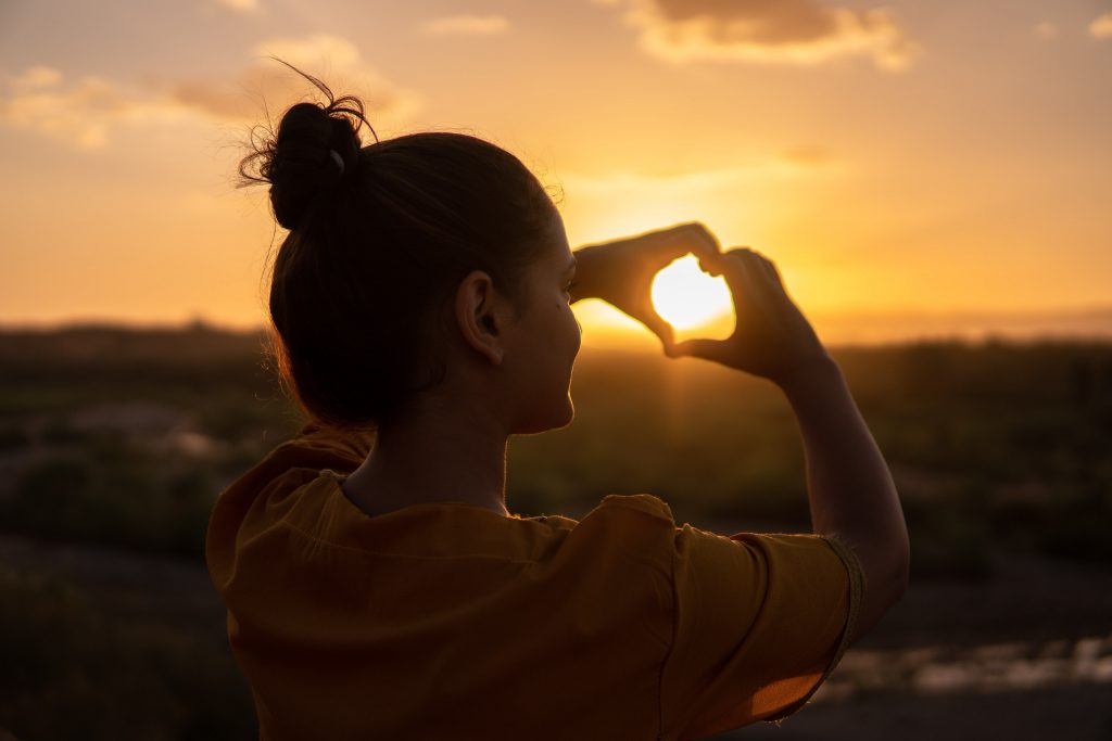 Girl making a heart with her hands in the sunset
